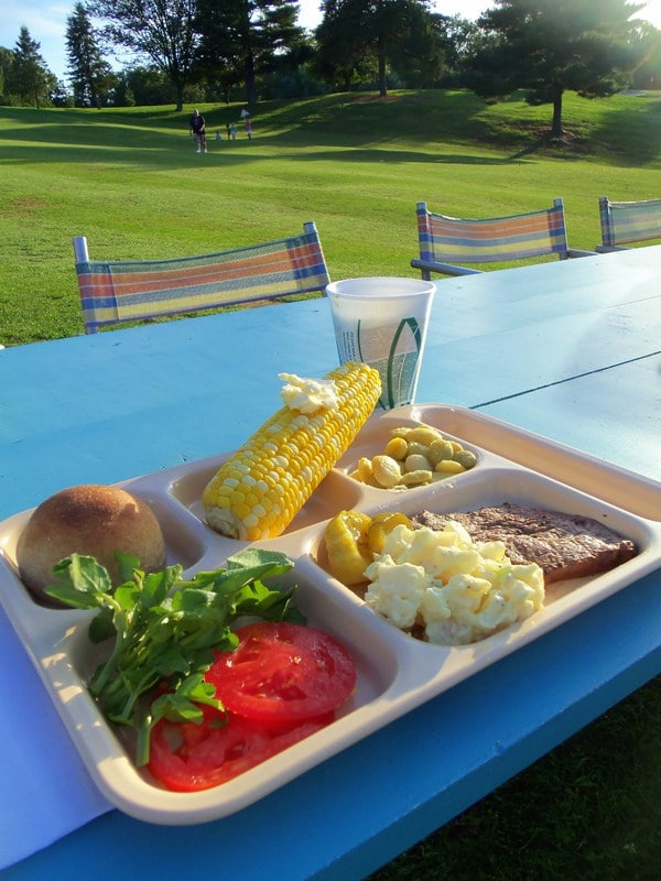 tray of food with buttered corn on the cob, tomatoes, lettuce, a roll, potato salad and steak